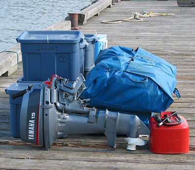 """A mound of gear on the dock at McBeth Point awaits the arrival of a Turbo Otter (below) for the return trip to """"civilization."""" As it turned out, the winds prevented the Otter from tying to the dock, and we had to carry the hundreds of pounds of gear all the way around the harbour and load from the float!"""