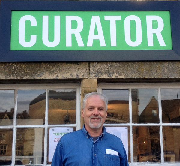 A curator stands outside a shop named Curator at Stow-on-the-Wold, England (photo by Katie Murphy)