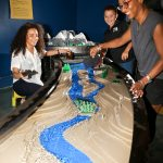 Family playing with watershed display