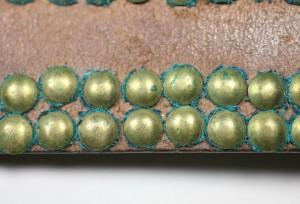 Deterioration of brass tacks on an ethnographic belt.