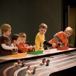 Kids racing model cars on racetrack