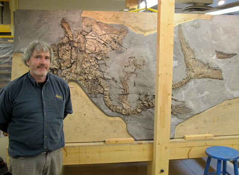 Kevin Conlin poses with a large fossil fish that he is preparing in Brandon