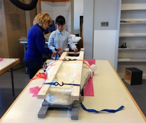 Janis Klapecki and Tamaki Sato, strapping the two cradles together.