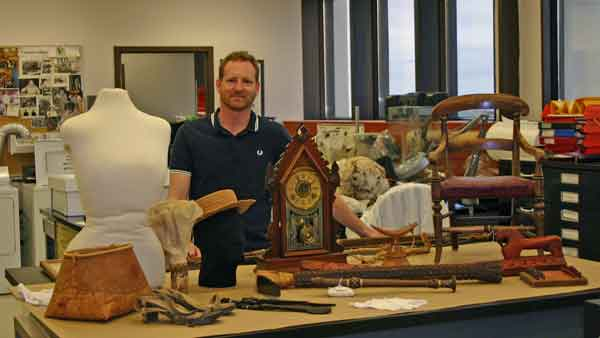 Curator of History, Roland Sawatzky, with wooden artefacts.