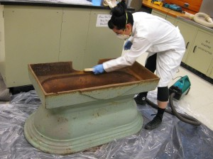 Conservator Lisa May cleans trough with a wire brush