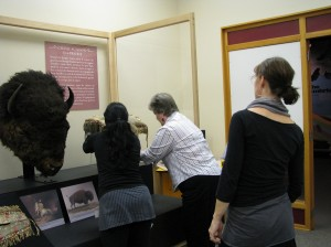 Conservator Lisa May and Collections Assistant Nancy Anderson adjust a saddle while Designer Stephanie Whitehouse looks on.